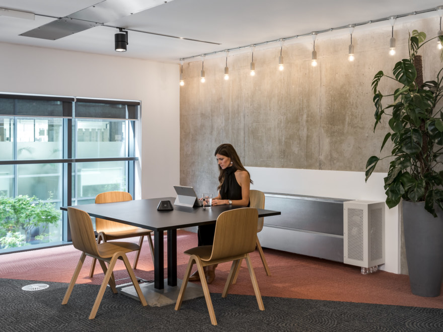 Private meeting room with a table and desks, and large windows. Used by one office member.